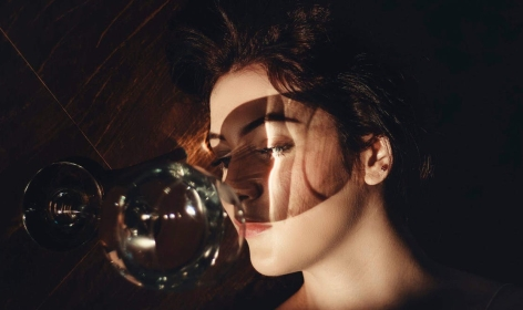 photo of woman lying beside a long stem clear wine glass